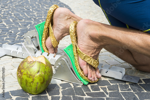 25198b1fabb6e3 Brazilian athlete wearing flip flops crouching at the start position in running  blocks with a coco gelado coconut on the tiles of the Copacabana boardwalk  ...
