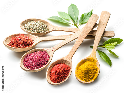 Photo Stands Spices Assortment of colorful spices in the wooden spoons on the white