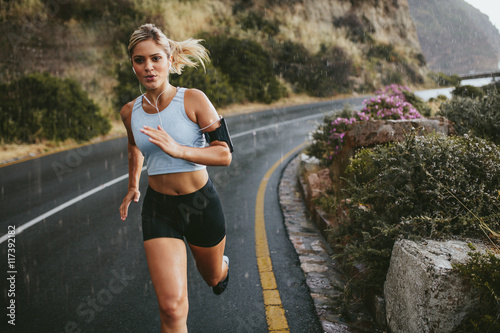 In de dag Jogging Female athlete running outdoors on highway