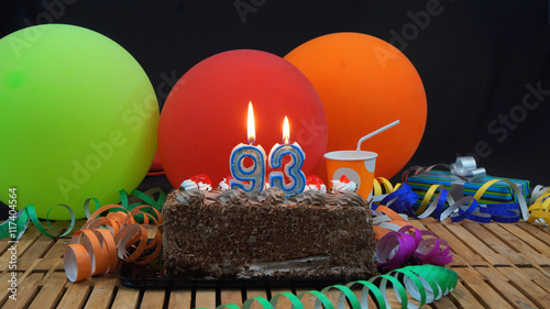 Valokuva  Chocolate birthday cake with candles burning on rustic wooden table with backgro