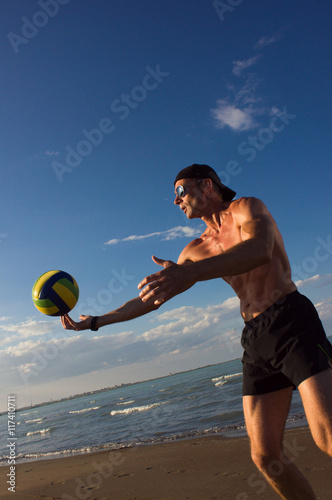 Beach volleyball. The player makes the pitch. - 117410711
