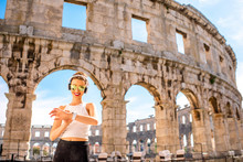 Young Sports Woman With Headphones And Smartwatch Resting After The Training Near The Ancient Coliseum In Pula City