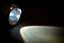 Flashlight And A Beam Of Light In Darkness. A Modern Led Light With Bright Projection On Dark Stone. Surface With Copy Space.