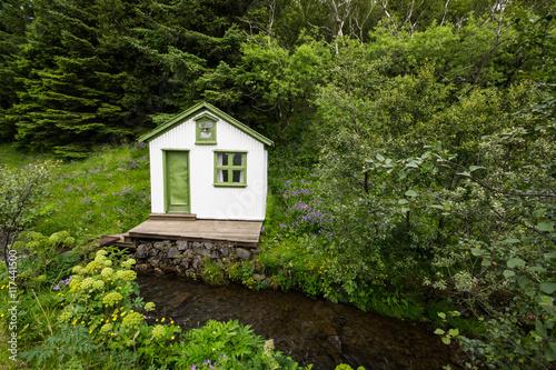 Fotografiet  Piccola casa immersa nel bosco in riva ad un fiume, Islanda