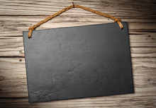 Black Slate Signboard On Aged Wooden Wall