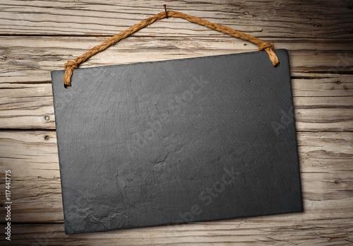 Fotografie, Obraz  black slate signboard on aged wooden wall