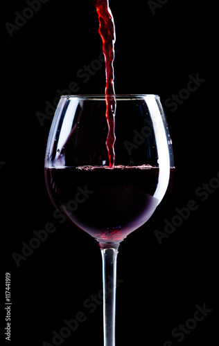 Pouring red wine into the glass - 117441919