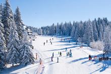 Panorama Of Ski Resort, Ski Slope, People Skiing, Houses Covered With Snow