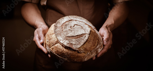 Fotografie, Obraz  Baker man holding a round bread