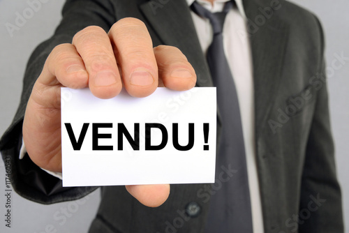 Fotografía  Homme inquilino une carte avec le mot vendu