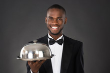 Waiter Serving Meal In Cloche