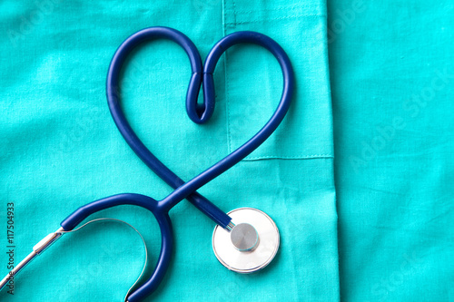 Valokuva  stethoscope shaping  heart and  clipboard on  medical uniform, closeup