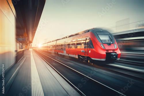 Fotografering Beautiful railway station with modern red commuter train at suns