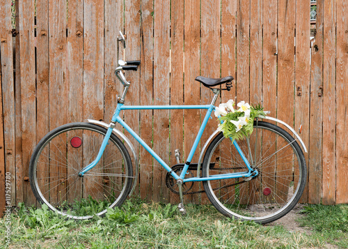 Photo sur Toile Velo Bouquet of lilies lying on the vintage bicycle. Photos near the old wooden fence.