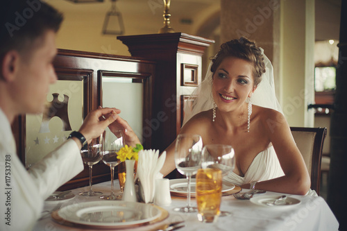 Fotobehang Restaurant Stunning bride holds groom's hand while sitting in the restauran