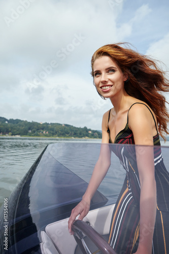 Poster Nautique motorise Summer vacation - young woman driving a motor boat
