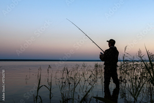 Foto op Canvas Vissen Fisherman silhouette at sunset on the lake while fishing