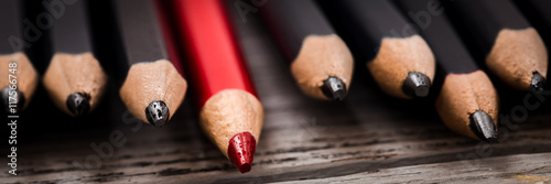 Red pencil stands out from the crowd of black  on a wooden white background Wallpaper Mural