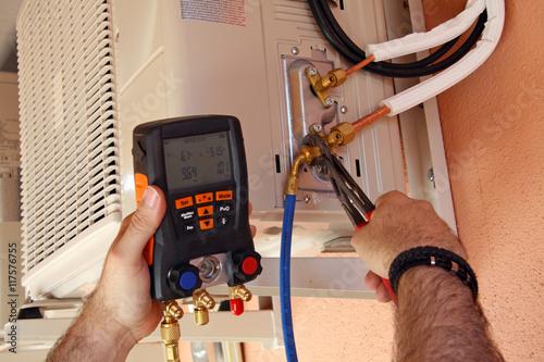 Instalador verificando el compresor de aire acondicionado Wallpaper Mural
