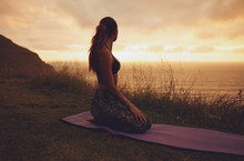Fitness Woman In Vajrasana Pose At Sunset