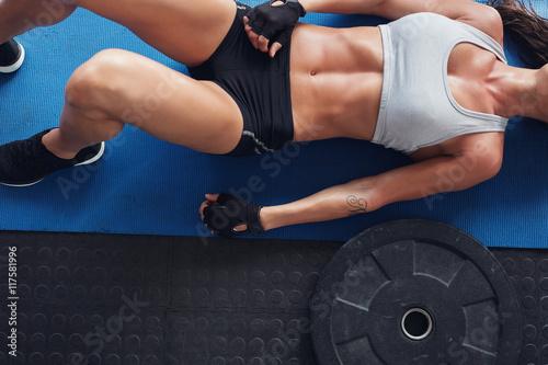 Foto  Muskulöse Frau, die auf Übungsmatte mit Gewichtsplatte