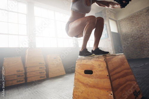 Fit young woman box jumping at a crossfit gym Canvas Print