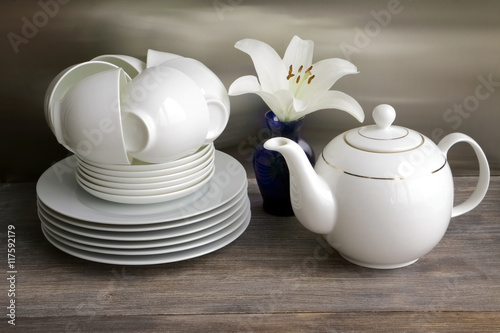 Foto White porcelain tea set - stacked cups and saucers and tea pot