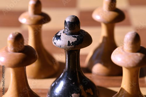 Photo  To be different: a black chessman between white chessmen