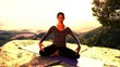 woman practices yoga clifftop setting at sunset