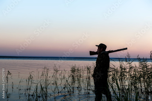 Foto op Canvas Jacht Hunter silhouette at sunset, while hunting on the lake