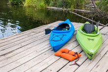 Two Colorfull Kayaks And Lifejacket On Dock