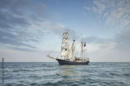 Tall Ship under sail with the shore in the background © janmiko