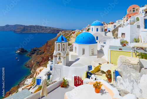 Poster Santorini Oia town on Santorini island, Greece. Traditional and famous houses and churches with blue domes over the Caldera, Aegean sea