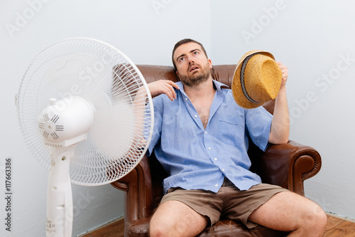 Fotografía  Flushed man feeling hot in front of a fan