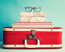 Eyeglasses Over Books And Vintage Suitcase