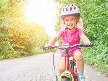 Happy Child Riding A Bike In O...