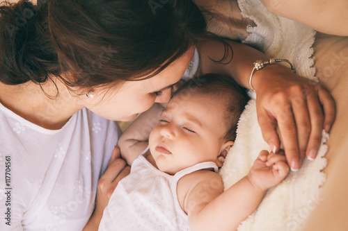 Photo  Beautiful young mom near sleeping 3 months baby.