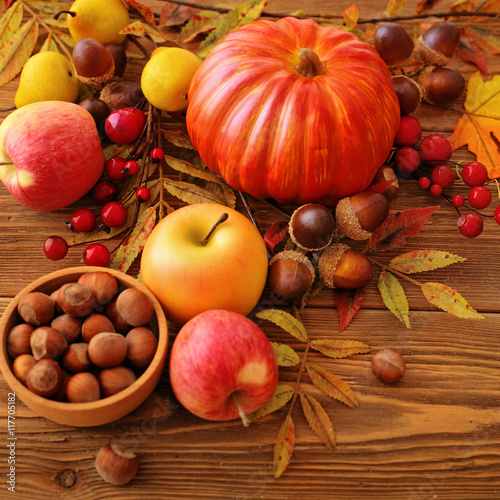 autumn fruits, flowers and leaves on wooden background - 117705182