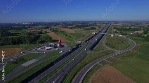 Highway countryside with cars traffic and gas station aerial 4K HD top view from above. Fly over road vehicles cars lorry trucks moving divided highway overpass bridge sunny day in Poland East Europe