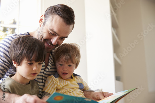 Fotografie, Obraz  Close Up Of Father And Sons Reading Story At Home Together