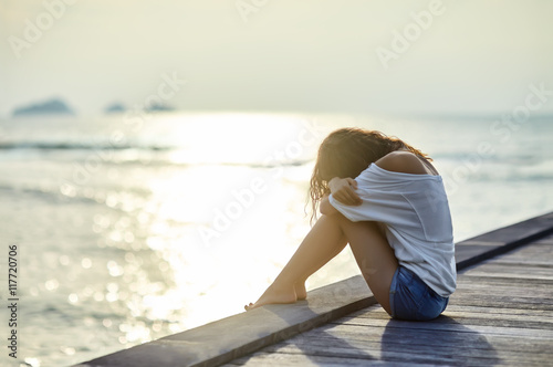 Fotografía  Sad lonely beautiful woman sitting on the pier