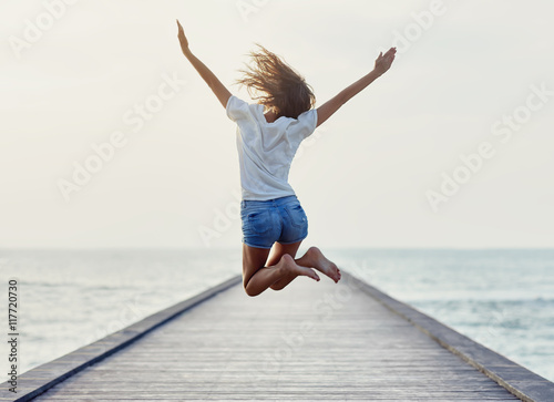 Photo Back view of jumping girl on the pier