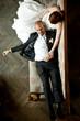 Stylish bald-headed groom lies on bride's knees