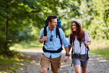 Happy Couple Hiking Together In Mountains With Backpacks