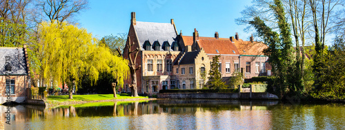 Poster Brugge Bruges, Belgium panorama with lake and medieval houses against blue sky