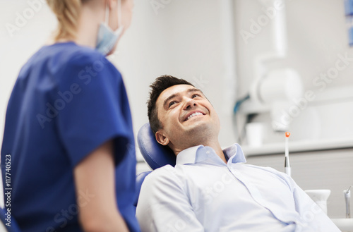 Fototapety, obrazy: female dentist with happy male patient at clinic
