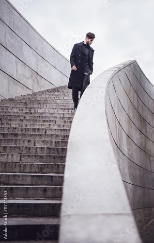 Plakat Young handsome trendy man with coat posing on stairs