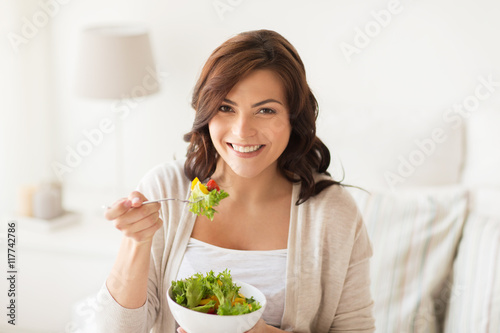 Fotobehang Kruidenierswinkel smiling young woman eating salad at home