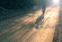 Single Man Walking On Countryside Road At Sunset.