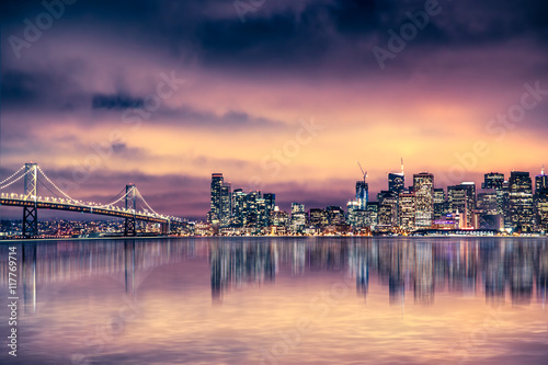 San Francisco California skyline with lights and bay under colorful sunset sky Poster